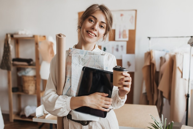 Lady in white blouse holds paper patterns and coffee cup