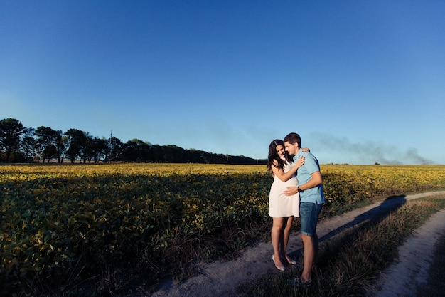 Lady in white dress hugs her man somewhere in the field