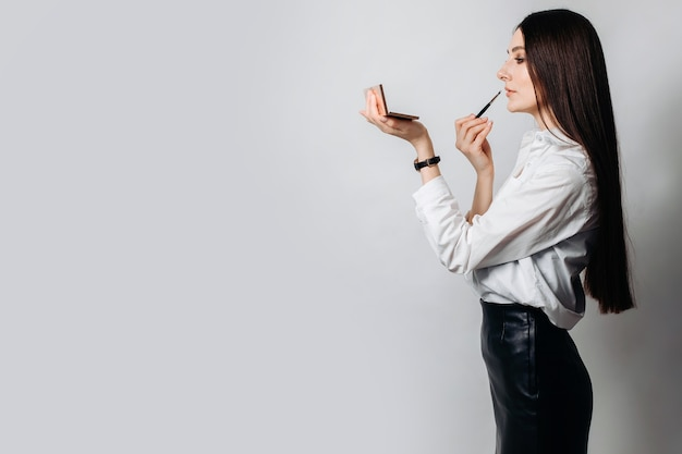 A lady in a white shirt does lip makeup with a brush. space for text on an isolated wall. the concept of beauty industry
