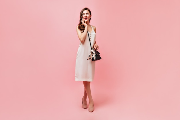 Lady in white summer dress smiles sweetly and holds handbag on pink background.