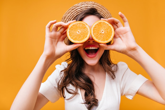 Lady in white top and straw hat laughs and covers her eyes with oranges.