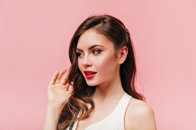 Lady in white top touches her wavy hair. shot of brunette woman with red lips on pink background.