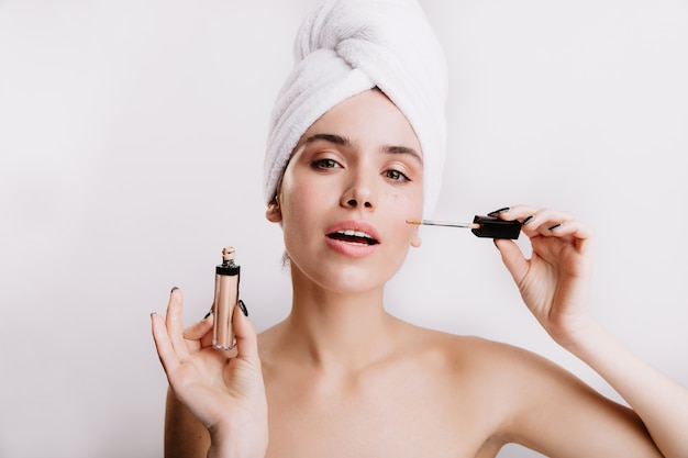 Lady in white towel on her head does nude makeup using concealer. close-up portrait of green-eyed girl on isolated wall.