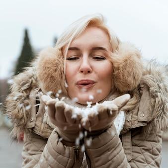 Signora in inverno che soffia nella neve