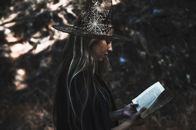 Lady in witch costume reading book