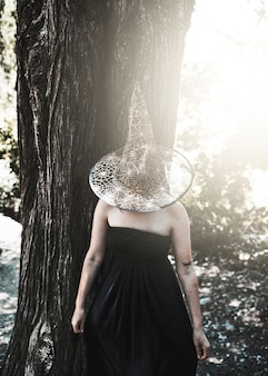 Lady in witch costume with closed face by hat standing near tree
