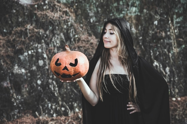 Lady in witch suit holding pumpkin