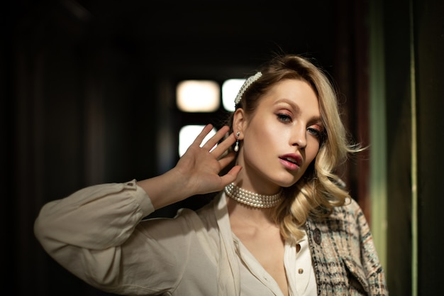 美しいメイクの女性が耳に触れます。白いブラウスと市松模様のジャケットのきれいなブロンドの女性は、暗い部屋でカメラをのぞきます