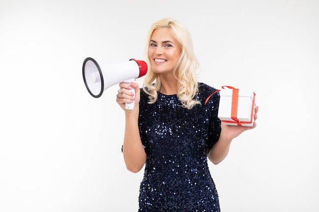 Lady with blond hair in a dress announces into a loudspeaker about a draw holding a gift box on a white studio background