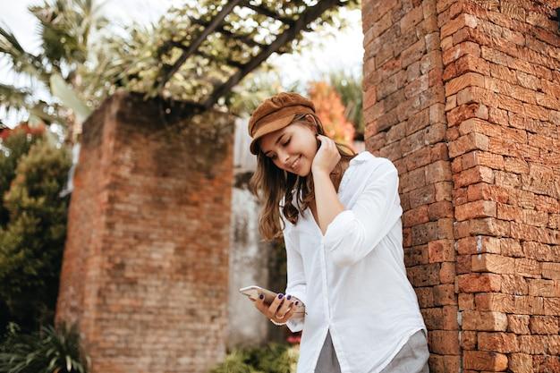 Signora con il manicure blu che tiene smartphone. ragazza in camicetta bianca e pantaloni grigi in posa vicino al muro di mattoni con piante tropicali.