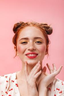 빵을 가진 아가씨는 분홍색 배경에 달콤한 오렌지와 미소로 그녀의 눈을 덮습니다.