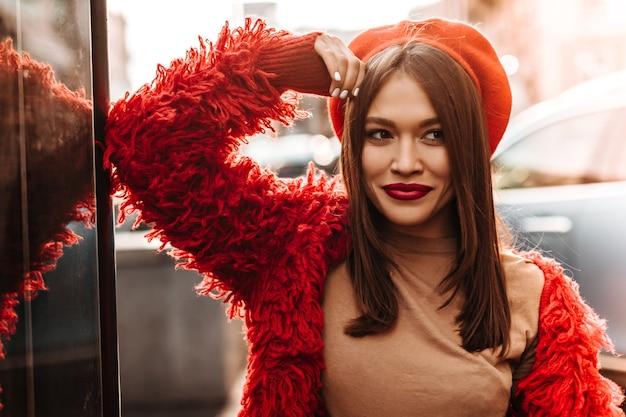 검은 스트레이트 머리와 갈색 눈을 가진 숙녀는 빨간 베레모와 유리 벽에 기대어 거리에서 포즈를 취하는 에코 코트를 입고 있습니다.