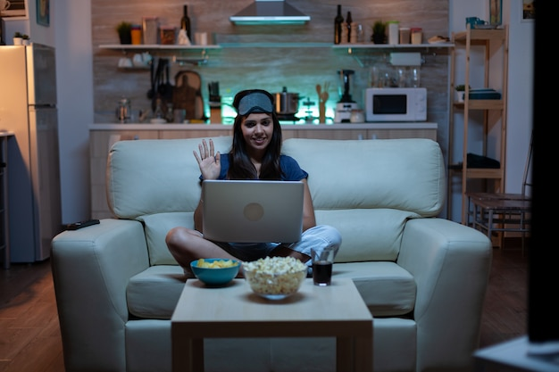 Lady with eye mask having video calling on laptop computer at night. exhausted person in pijamas talking on notebook computer webcam with colleagues sitting on couch at home using internet technology
