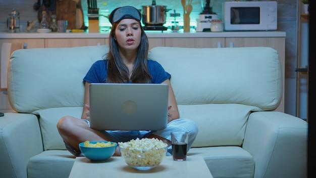 夜にラップトップコンピューターでビデオ通話をしているアイマスクを持つ女性。インターネット技術を使用して自宅のソファに座っている同僚とノートブックコンピューターのウェブカメラで話しているパジャマで疲れ果てた人