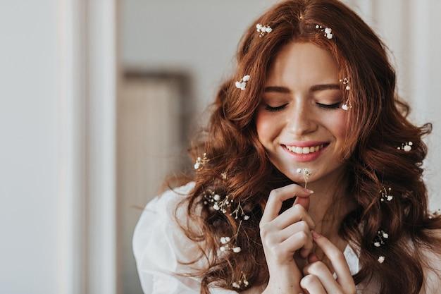 笑顔のポーズで赤いカールの花を持つ女性。彼女の手に小さな植物を持つ女性の屋内の肖像画。