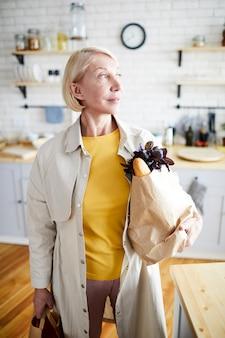 キッチンでフルバッグを持つ女性