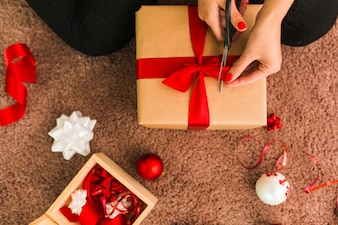 Lady with gift box and scissors near decorative bows, balls and ribbon on carpet