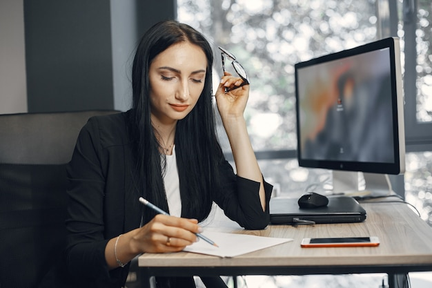 Lady with glasses. manager is sitting at the computer. businesswoman works in her office.