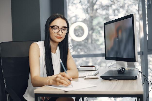 Signora con gli occhiali. il manager è seduto al computer. la donna di affari lavora nel suo ufficio.