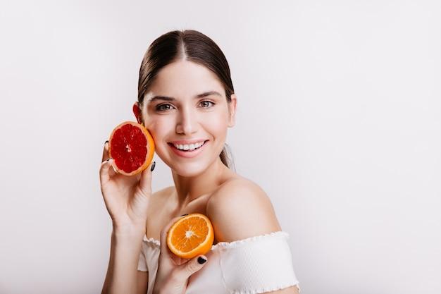 Signora con gli occhi verdi in cima bianca che posa sulla parete isolata senza filtri e trucco. la donna tiene arancia e pompelmo vicino al viso.
