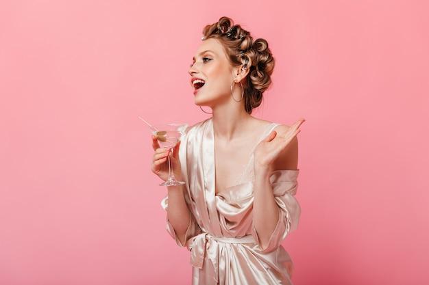 ヘアカーラーとバスローブを着た女性が笑い、孤立した壁にマティーニグラスでポーズをとる