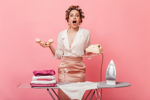 Lady with hair curlers looks amazed while holds retro telephone
