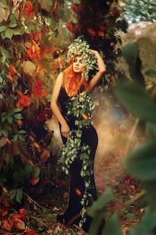 頭にホップと屋外でポーズをとる魔法の森で素敵なメイクの女性