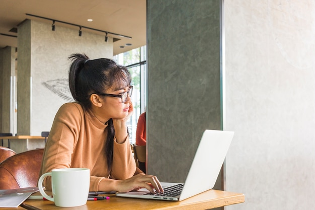 テーブルでノートパソコンを持っている女性