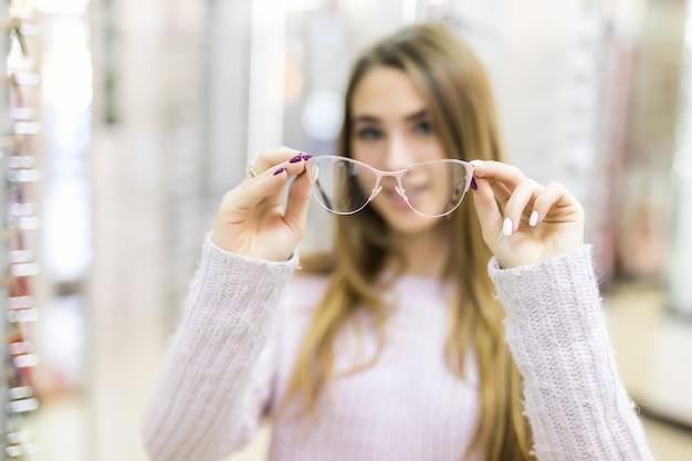 金の長い髪とモデルの外観を持つ女性は、専門店でメガネの違いを示します