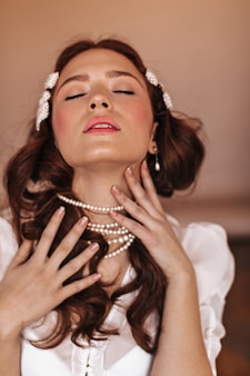 Lady with pearl hairpins strokes her neck with pleasure. woman in white blouse posing with closed eyes.