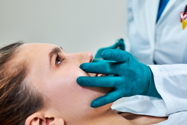 Lady with plaster on nose, doctor examining patients face after plastic surgery.