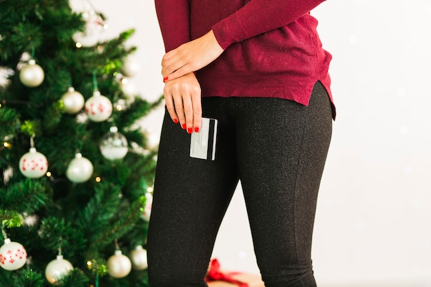 Lady with plastic card near christmas tree