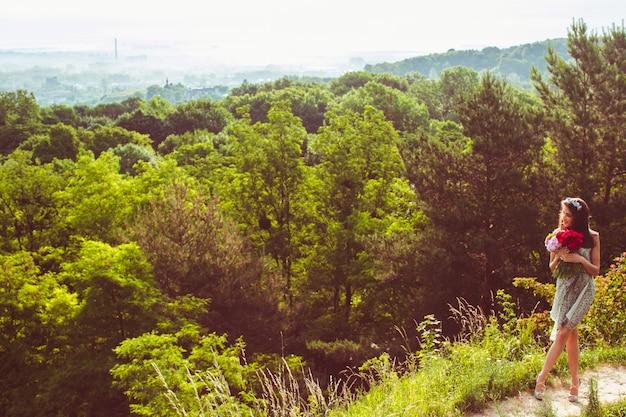 Леди с красным букетом стоит на зеленом холме