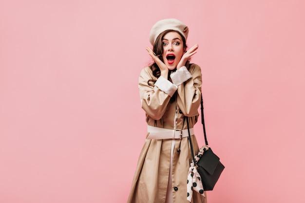 Дама с красными губами удивленно смотрит в камеру. женщина в стильном плаще позирует с сумкой через плечо на розовом фоне.