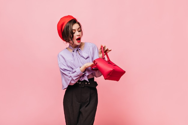 Lady with red lips looking into bag. portrait of girl in hat and elegant outfit on pink background.