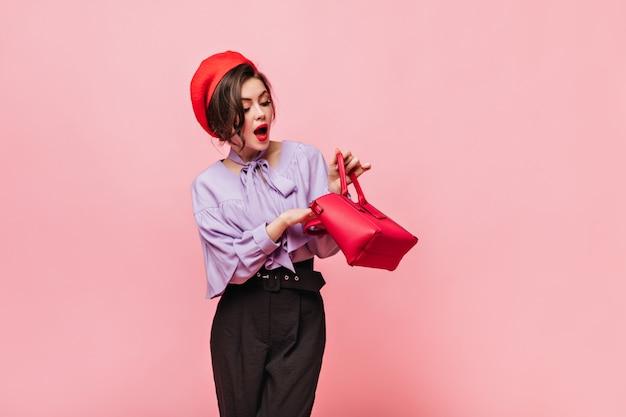 가방을 찾고 붉은 입술을 가진 아가씨입니다. 모자와 분홍색 배경에 우아한 옷에 여자의 초상화.