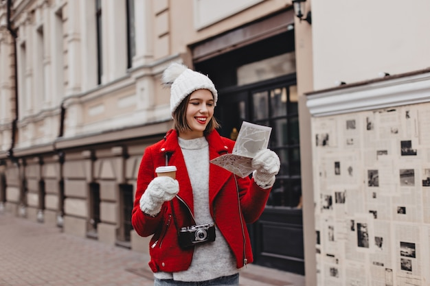 Lady with red lipstick dressed in white hat, gloves and short wool coat is holding glass of tea and paper card, posing outdoors with retro camera.