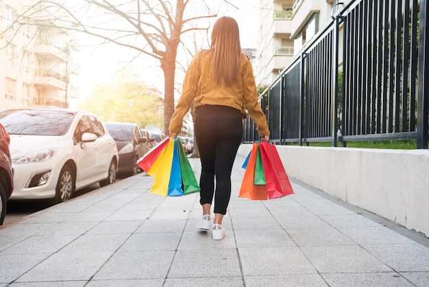 Lady with shopping packets going on street