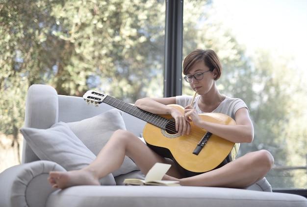 짧은 검은 머리와 소파에서 기타를 연주하는 안경 아가씨