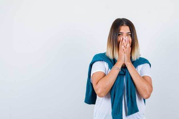 白いtシャツを着て手で口を覆い、陽気に見えるセーターを結んだ女性。正面図。
