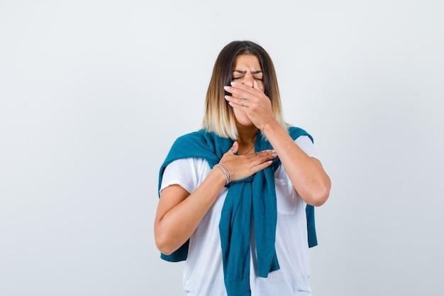 Дама со связанным свитером в белой футболке зевает и выглядит сонной, вид спереди.