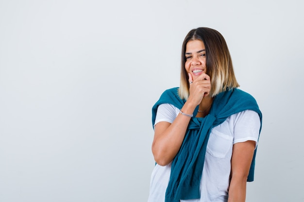 Lady with tied sweater in white t-shirt with hand on chin and looking cheerful , front view.