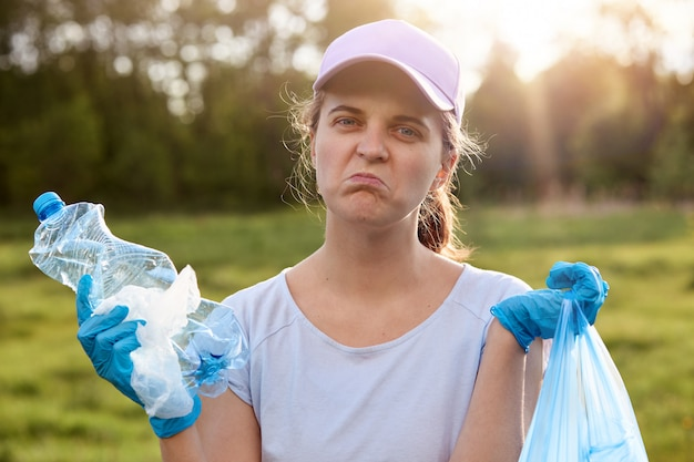 Lady with twisted face wearing blue latex gloves, holding rubbish in hands,  with upset facial expression, wants to clean up planet from litter and reusing waste, ecological problems.