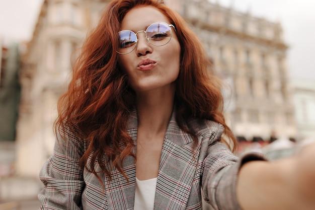 Дама с вьющимися волосами посылает воздушный поцелуй и делает селфи на улице
