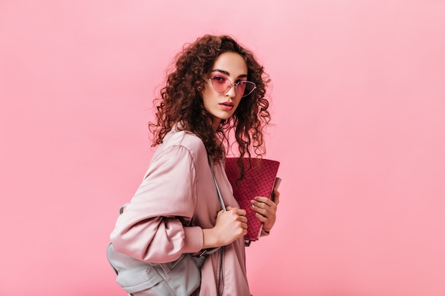 Дама с вьющимися волосами смотрит в камеру и держит книги