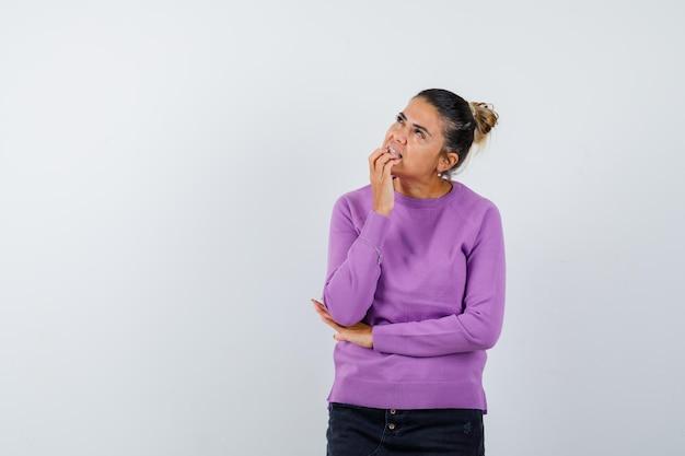 Signora in camicetta di lana che tiene la mano sul mento e sembra sognante