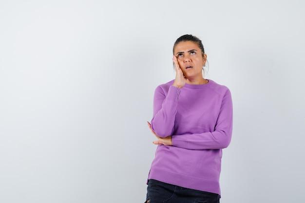 Signora in camicetta di lana appoggiata guancia sul palmo e guardando pensierosa