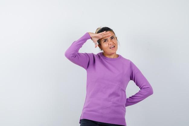 Signora in camicetta di lana che guarda lontano con la mano sopra la testa e sembra pensierosa