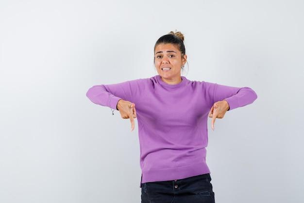 Signora in camicetta di lana che punta verso il basso e sembra allegra