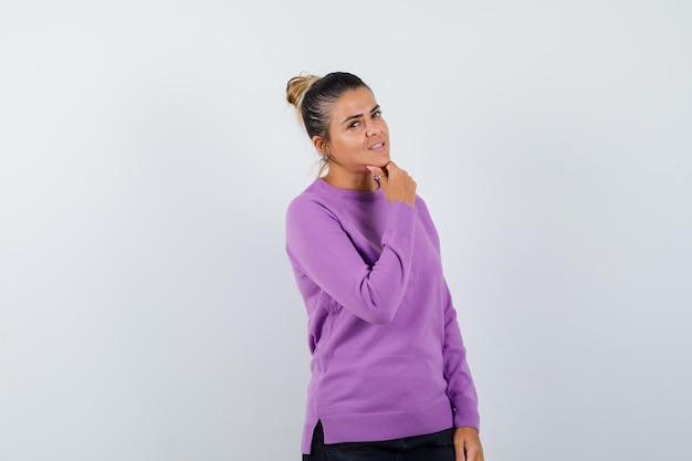 Signora in camicetta di lana che appoggia il mento sulla mano e sembra sicura